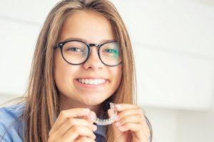 girl holding Invisalign clear aligner