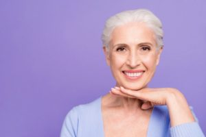 Smiling older woman with dental implants in Jupiter on purple background