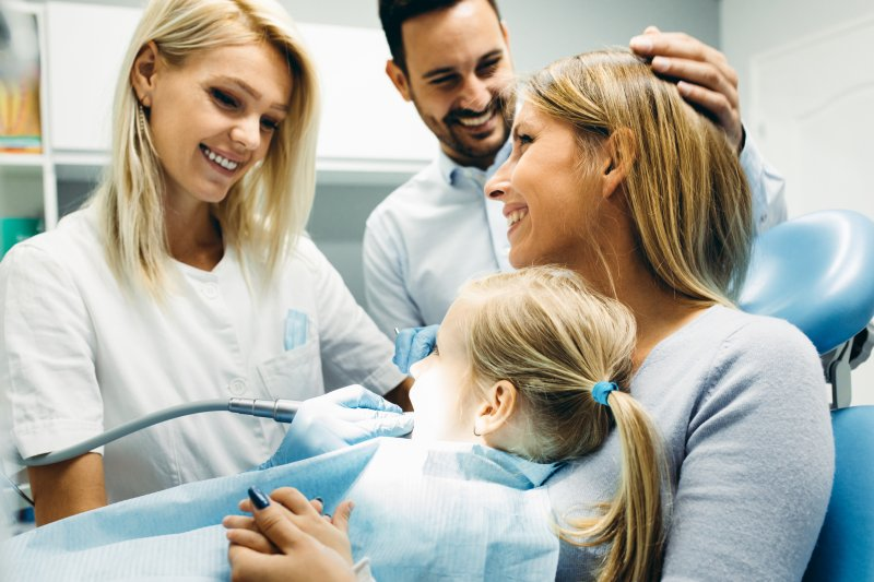 Family smiling at child's dentist appointment